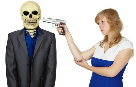 threatens: The young woman threatens with a pistol to the person - skeleton