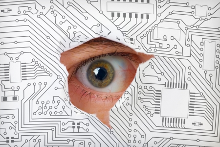 industrial espionage: Human eye looking through a hole in the electronic circuit Stock Photo