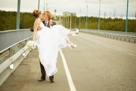 The groom carries his bride in his arms on the bridge