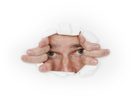 A man looks out from a hole in the white paper photo
