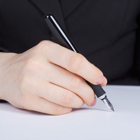 Female hand holding a fountain pen with a silver pen photo