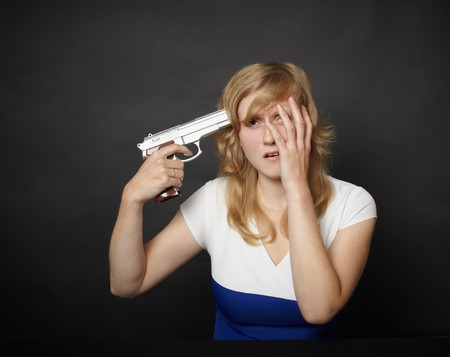 A young woman is going to commit suicide with a gun photo