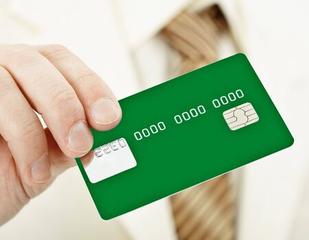 electronic card: The person holds a green electronic plastic card in a hand