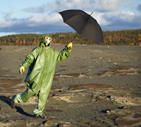 The comical person in protective scientific overalls with an umbrella in a hand Stock Photo - 8271602