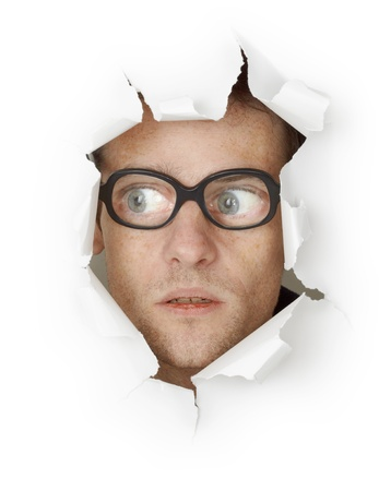 Funny man in an old-fashioned glasses looking out of the hole isolated on white background photo
