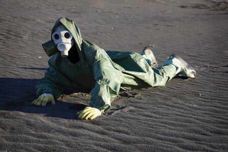 Man in gas-mask crawling through the desert land photo