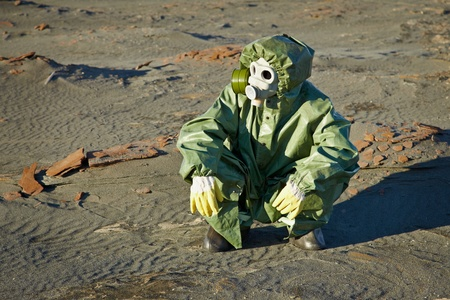 Scientist in a green protective suit and gas mask sitting on the slag Stock Photo - 8271897