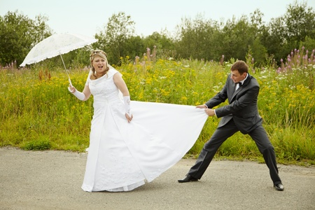 Funny bride and groom having fun outdoors photo
