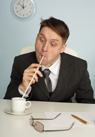 Comic man is drinking coffee with long straws in office Stock Photo - 8337290
