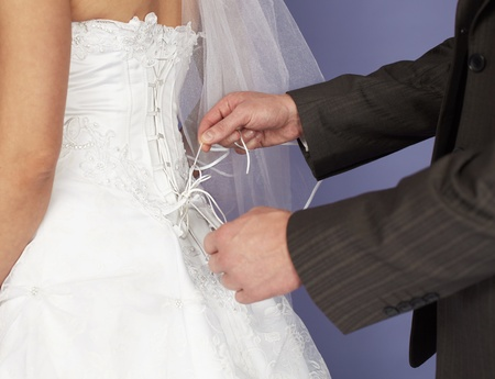 The groom unties a corset to the bride