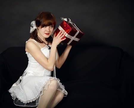 The happy young girl has received a gift on dark background photo