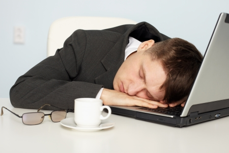 A young businessman not enough sleep and fell asleep on the job photo