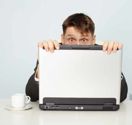 concealment: Official frightened and hides behind a laptop Stock Photo