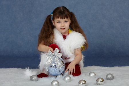 The child sits on a blue background with Christmas tree ball photo