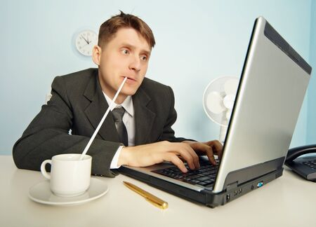 The amusing businessman drinks coffee through a straw without distracting from work in the Internet photo