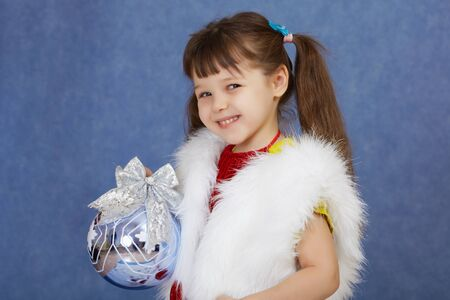 The little girl in a white fur costume holding a glass ball on blue photo