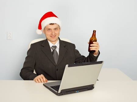 necktie beer: Office clerk begins to celebrate Christmas at work Stock Photo