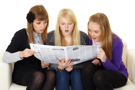 Three young girls are reading a newspaper on white photo