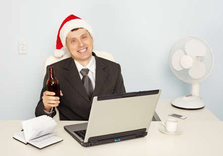 necktie beer: A young businessman gets drunk at the office before the new year Stock Photo