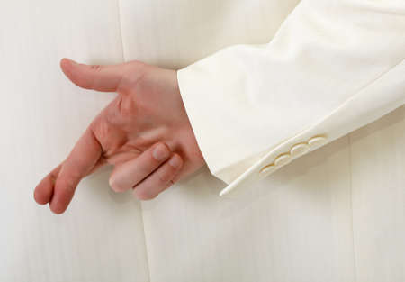 Fingers crossed behind back - man in white suit Stock Photo - 8468514