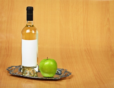 stilllife: Still-life - a bottle of white wine and a green apple on a tray Stock Photo