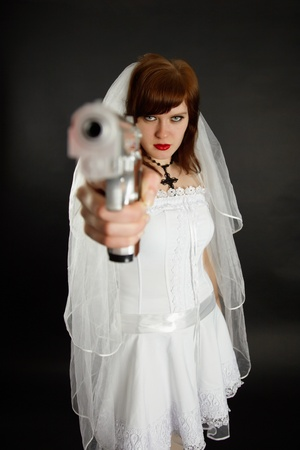 marriageable: Young bride threatens us with a gun on black background