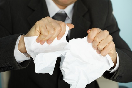 tormented: Businessman violently tormented the paper in his hands Stock Photo