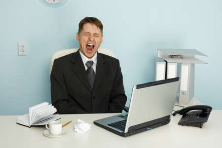 ennui: Businessman yawning from boredom and idleness in the office