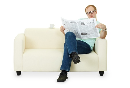 evening newspaper: A man reading a newspaper at home sitting on the sofa Stock Photo