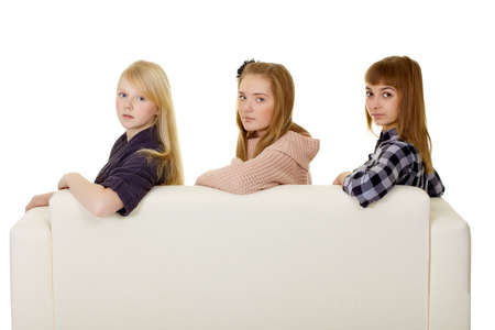 Three young girls - classmate sitting on the couch photo