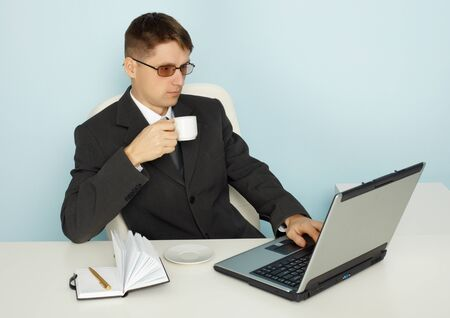 news online: Business man reads the news online and drinking coffee
