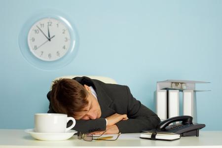 tired man sleeping on a table next to mug and phone  photo