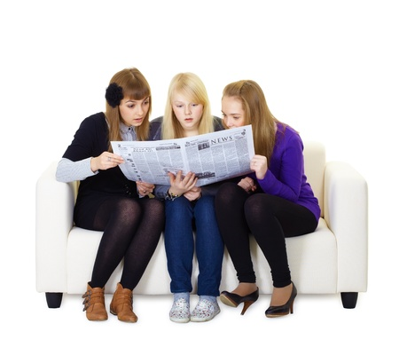 Three girlfriends teen read with interest newspaper sitting on the couch photo