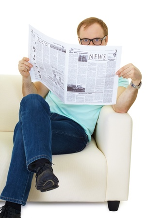 man sitting on the couch reading a newspaper.  photo