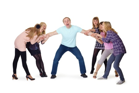 joyful girl pulled a man confused by the arms in opposite directions  photo