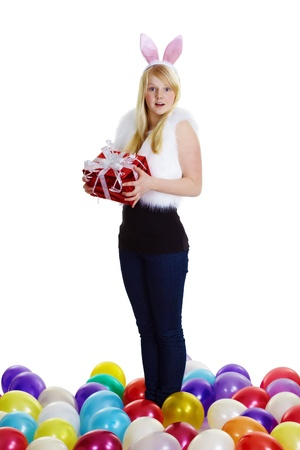 girl dressed as a rabbit with a gift in his hands and balloons on a white background  photo