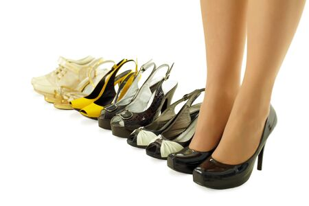several: female legs in high heels and a number of different summer shoes  Stock Photo