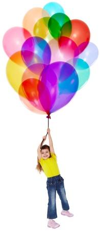 volar: La niña está volando sobre un montón de globos de color