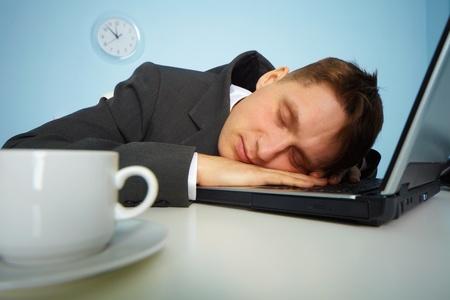 durmiendo: hombre cansado, durmiendo en un teclado de ordenador port�til durante la noche en la Oficina  Foto de archivo