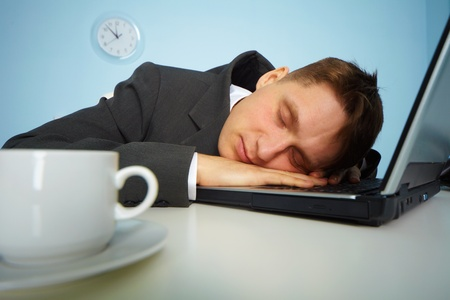 place of work: tired man sleeping on a notebook keyboard at night in the office  Stock Photo