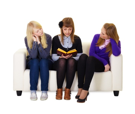 ennui: Teen girl reading a book to her friends sitting on the couch