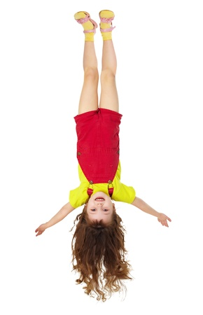 Cheerful little girl hangs upside down isolated on white background photo