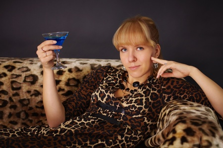 Girl in leopard dress, drinking a cocktail on sofa Stock Photo - 8978599
