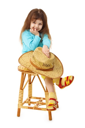 The child sits on an old wooden chair with a straw hat in hand isolated on white background Stock Photo - 8978478