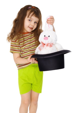 A child gets a rabbit out of a hat like a magician isolated on white background photo