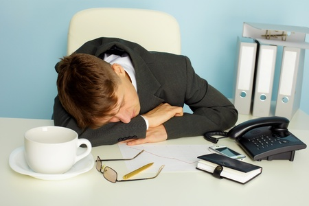 The young man fell asleep on the desktop in the office Stock Photo - 8978600