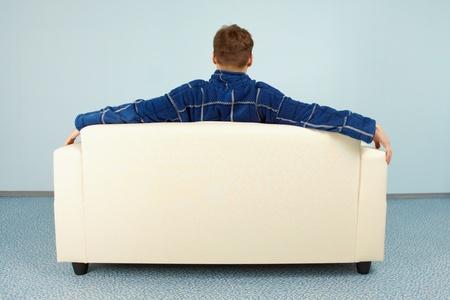 Un jeune homme est assis confortablement à la maison sur le divan