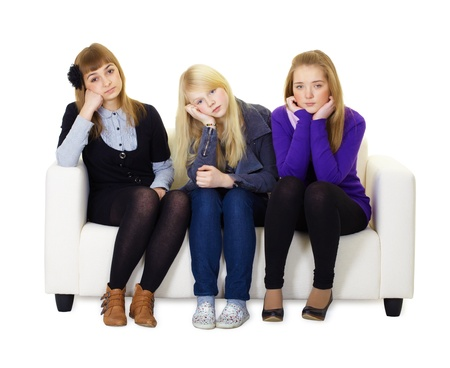 ennui: Three bored friends sitting on the couch. White isolated background Stock Photo