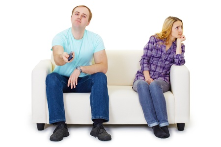 indifferent: A husband and wife in a quarrel sit on the couch watching TV isolated on white background Stock Photo
