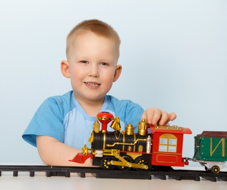 Little boy playing with a toy locomotive on blue background photo